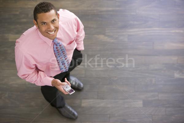 Zakenman permanente binnenshuis mobieltje glimlachend man Stockfoto © monkey_business