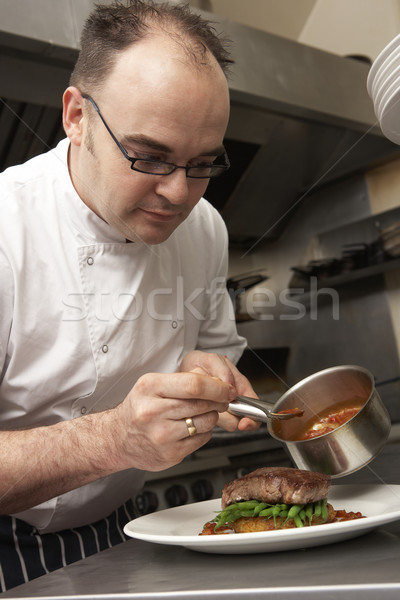 Chef Adding Sauce To Dish In Restaurant Kitchen Stock photo © monkey_business