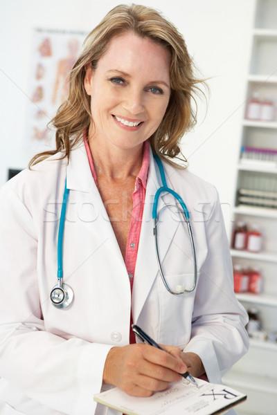 Mid age female doctor writing prescription Stock photo © monkey_business