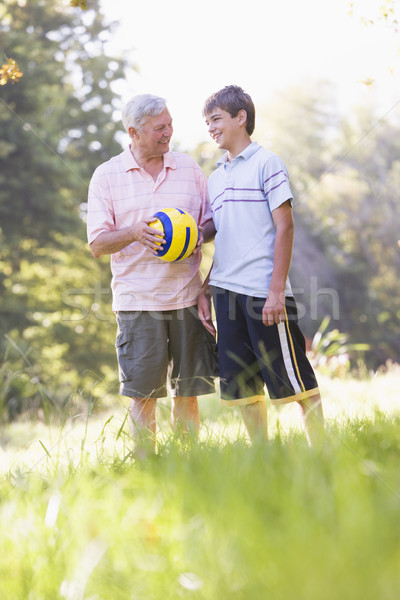 Grandfather and grandson at a park holding a ball and smiling Stock photo © monkey_business