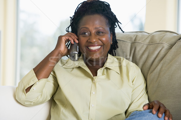 Stock photo: Woman sitting in living room using telephone and smiling
