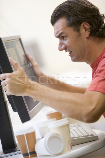 Stock photo: Man in computer room with many empty cups of coffee grabbing his