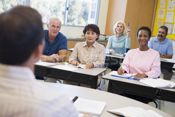Mature female student raising hand in class Stock photo © monkey_business