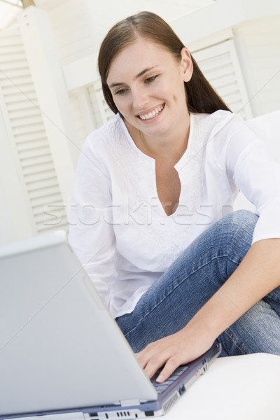 Woman on patio using laptop and smiling Stock photo © monkey_business