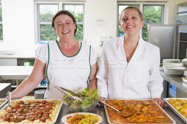 Lunchladies beside trays of food in school cafeteria Stock photo © monkey_business