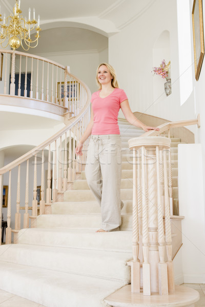 Woman coming down staircase in luxurious home smiling Stock photo © monkey_business