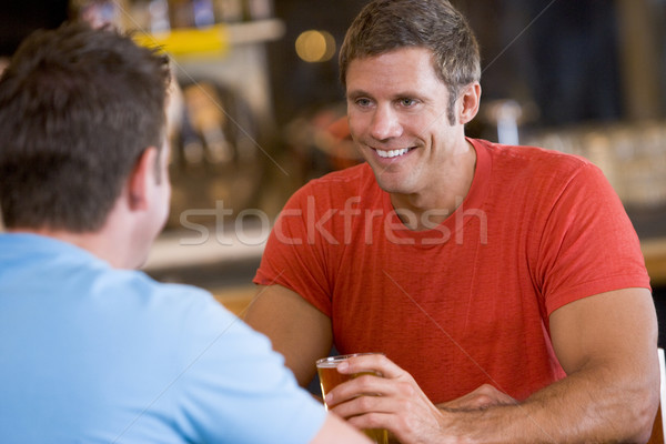 Two men talking over beer in a bar Stock photo © monkey_business