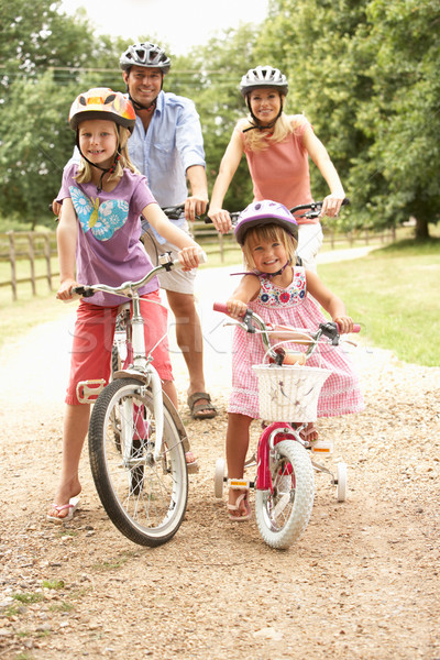 Family Cycling In Countryside Wearing Safety Helmets Stock photo © monkey_business