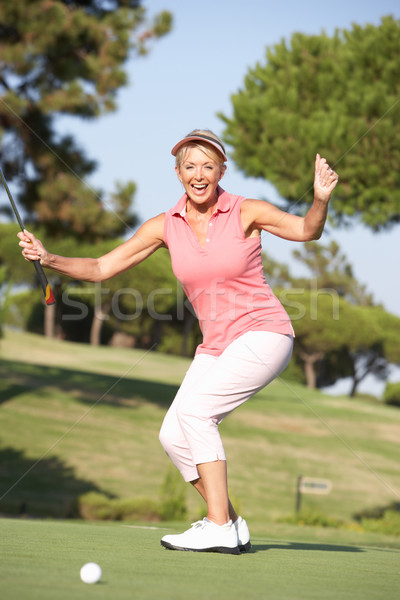 Senior Female Golfer On Golf Course Lining Up Putt On Green Stock photo © monkey_business
