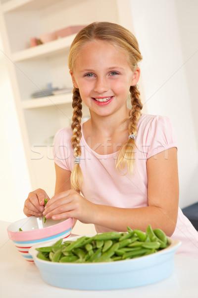 Happy girl splitting peas in kitchen Stock photo © monkey_business