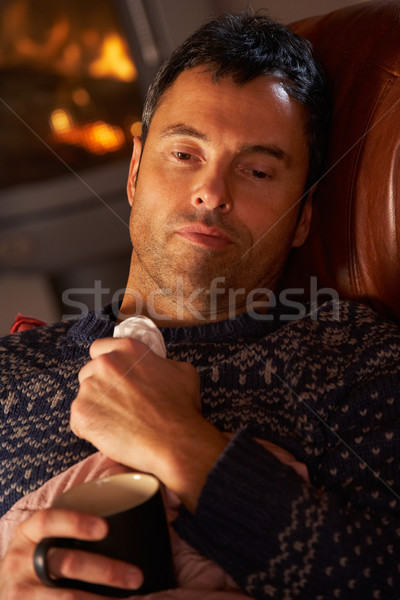 Sick Man With Cold Resting On Sofa By Cosy Log Fire Stock photo © monkey_business