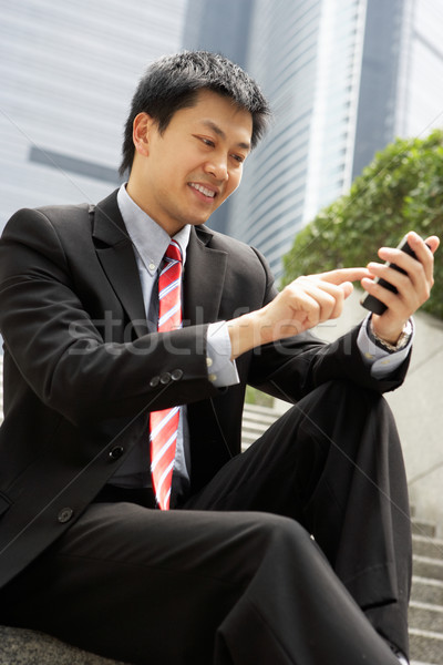 Chinese Businessman Dialling On Mobile Phone Outside Office Stock photo © monkey_business
