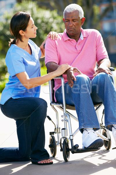 Carer Pushing Unhappy Senior Man In Wheelchair Stock photo © monkey_business