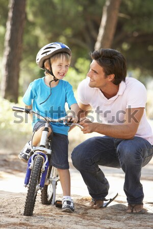 Father Teaching Daughter To Ride Bike In Garden Stock photo © monkey_business
