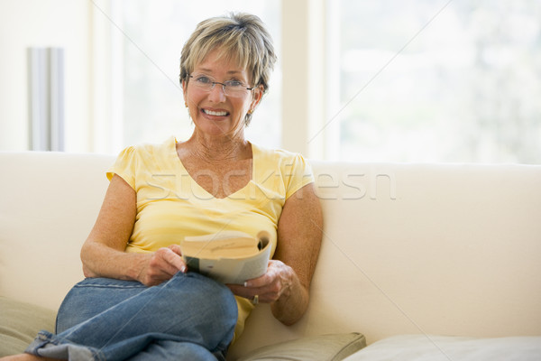 Woman relaxing with book in living room and smiling Stock photo © monkey_business