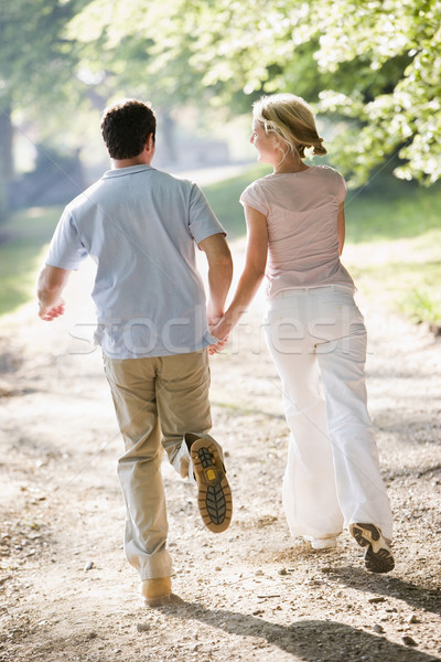 Stock photo: Couple running outdoors holding hands