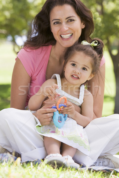 Femme jeune fille séance extérieur jouet femme souriante Photo stock © monkey_business