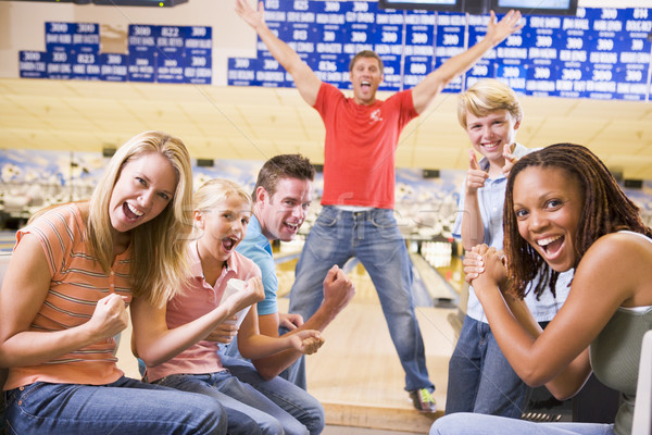 Stock photo: Family in bowling alley with two friends cheering and smiling