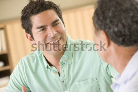 Two men sitting in living room talking and smiling Stock photo © monkey_business