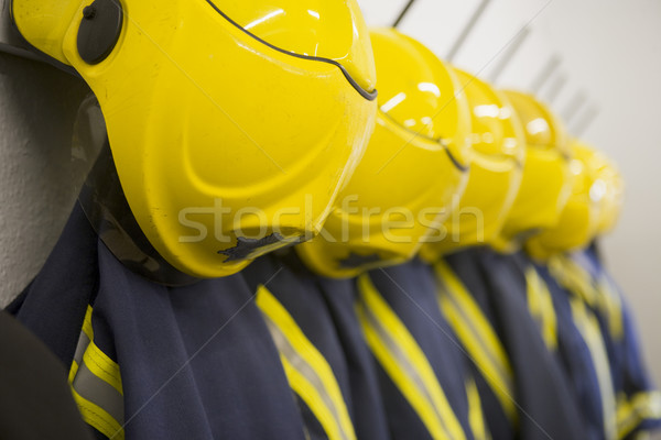 Firefighter's coats and helmets hanging up in a fire station Stock photo © monkey_business