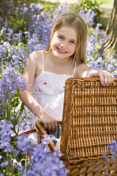 Stock photo: Young girl sitting outdoors with picnic basket smiling