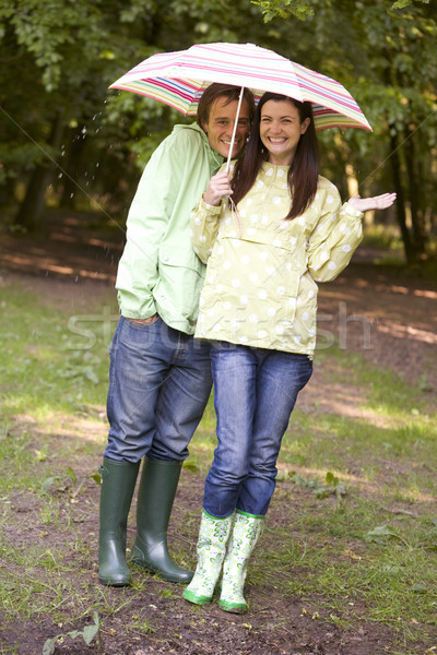 Couple outdoors in rain with umbrella smiling Stock photo © monkey_business