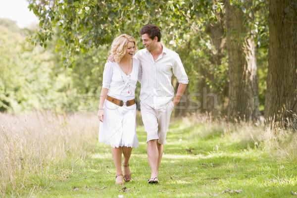 Couple walking on path smiling Stock photo © monkey_business