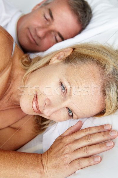 Stock photo: Mid age couple in bed woman awake