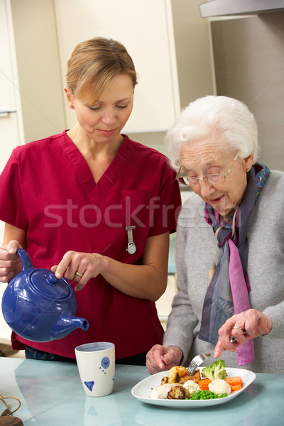 Senior woman with carer eating meal at home Stock photo © monkey_business