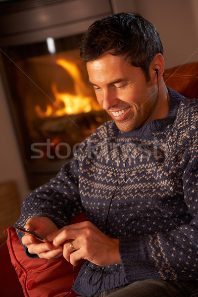 Middle Aged Man Using MP3 Player By Cosy Log Fire Stock photo © monkey_business