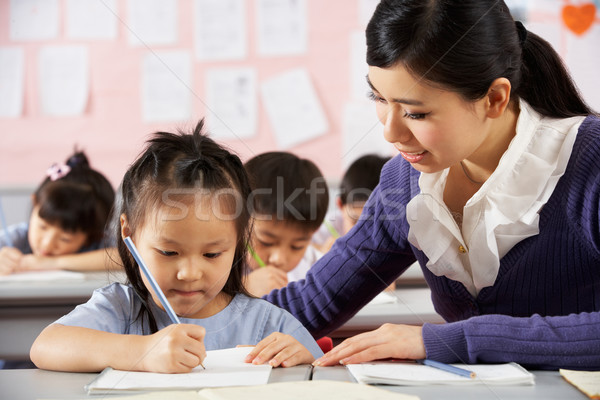 Teacher Helping Student Working At Desk In Chinese School Classr Stock photo © monkey_business