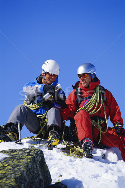 Young men mountain climbing on snowy peak Stock photo © monkey_business