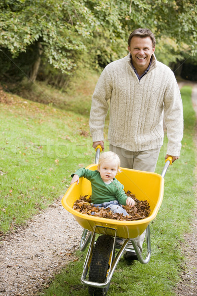 Father pushing young son in wheelbarrow Stock photo © monkey_business