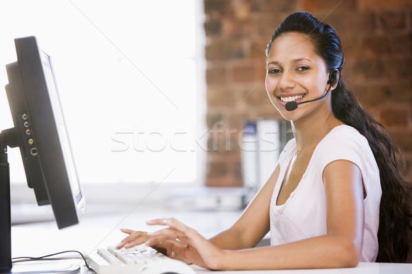 Mujer de negocios oficina auricular escribiendo ordenador Foto stock © monkey_business