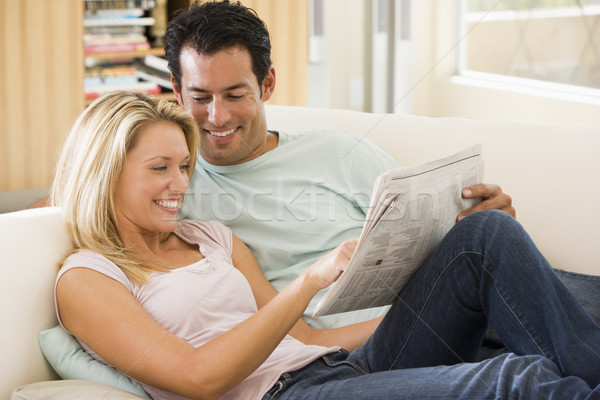 Couple in living room reading newspaper and smiling Stock photo © monkey_business