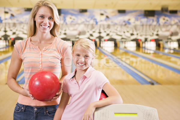 Stock photo: Woman and young girl in bowling alley holding ball and smiling