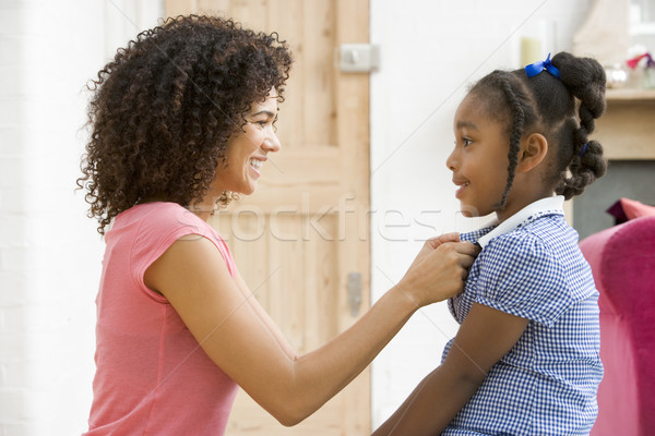 Woman in front hallway fixing young girl's dress and smiling Stock photo © monkey_business