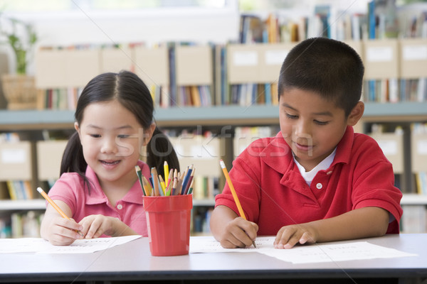 Kindergarten children sitting at desk and writing in classroom Stock photo © monkey_business