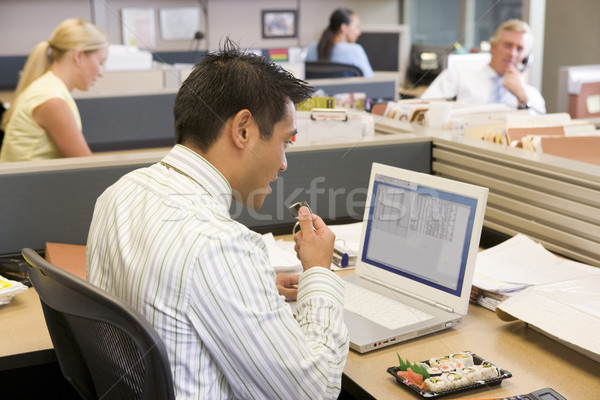 Businessman in cubicle at laptop eating sushi Stock photo © monkey_business