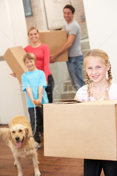 Family with dog on moving day carrying cardboard boxes Stock photo © monkey_business