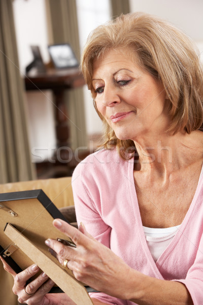 Senior Woman Looking At Photograph In Frame Stock photo © monkey_business