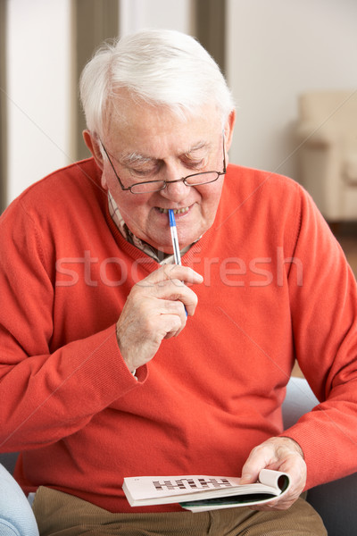 Senior Man Relaxing In Chair At Home Completing Crossword Stock photo © monkey_business