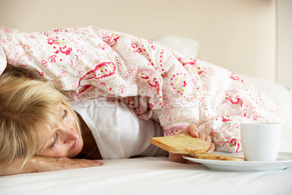Senior Woman Snuggled Under Duvet Eating Breakfast Stock photo © monkey_business