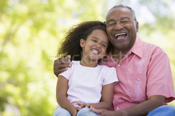 Grandfather and granddaughter outdoors smiling Stock photo © monkey_business
