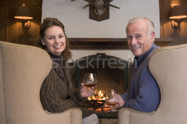 Couple sitting in living room by fireplace with drinks smiling Stock photo © monkey_business