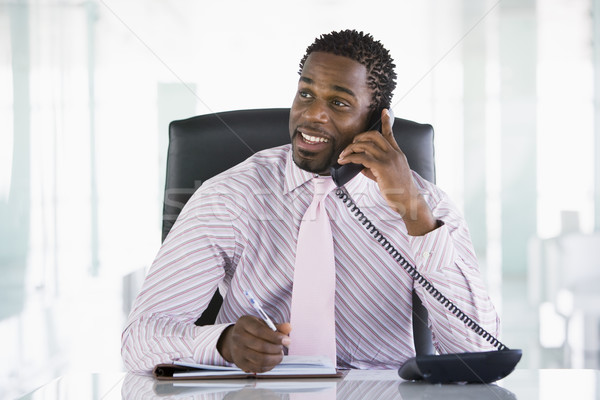 Businessman sitting in office with personal organizer open on te Stock photo © monkey_business