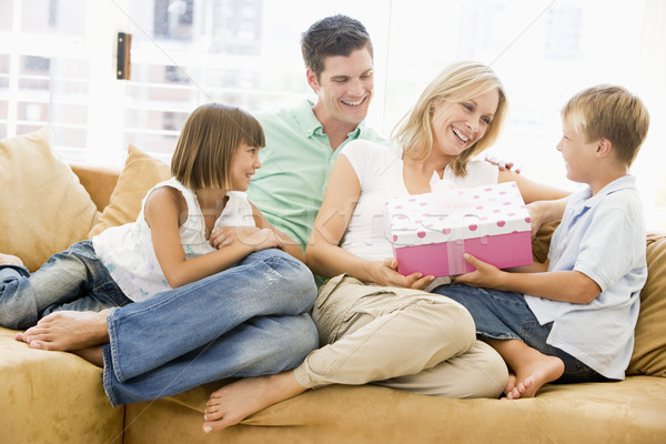 Family in living room with mother receiving gift and smiling Stock photo © monkey_business