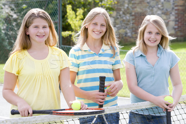 Three young girl friends with rackets on tennis court smiling Stock photo © monkey_business