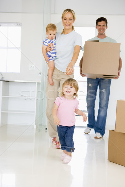 Stock photo: Family with box moving into new home smiling