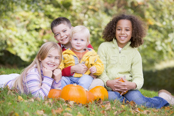 Three young friends with baby sitting on grass with pumpkins smi Stock photo © monkey_business